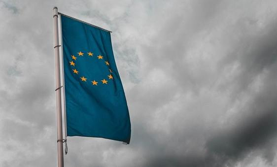 European Union flag against a dark, stormy sky background